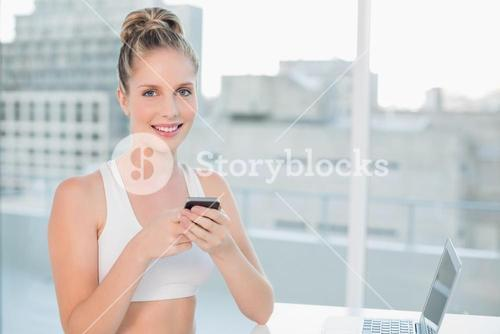 Cheerful sporty blonde sending a text
