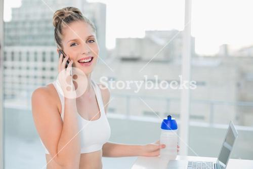 Laughing sporty blonde on the phone