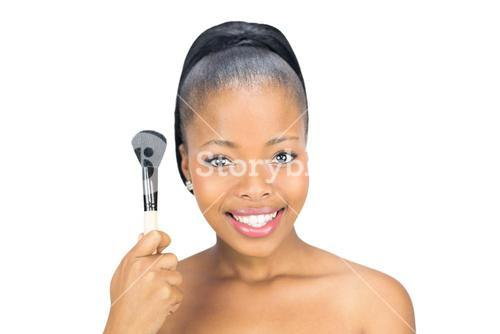 Woman holding makeup brush to face
