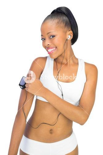 Smiling woman in sportswear using music player while looking at camera