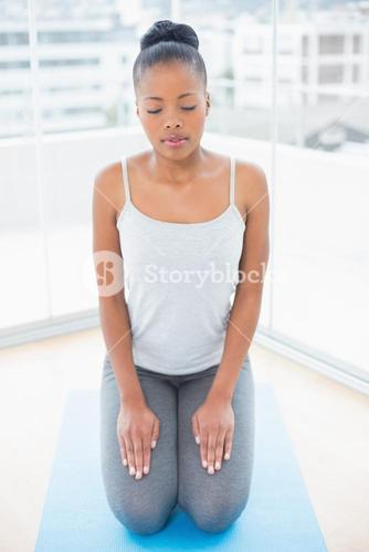 Peaceful woman sitting on blue exercise mat
