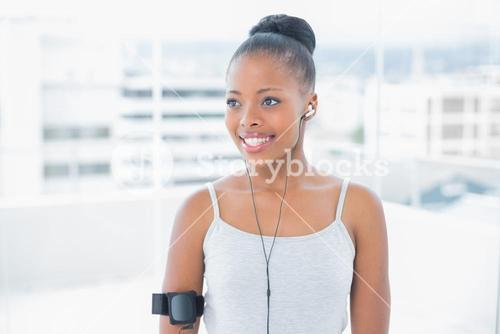 Smiling attractive woman in sportswear listening to music