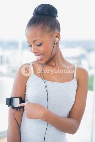 Smiling woman in sportswear listening to music and using her music player