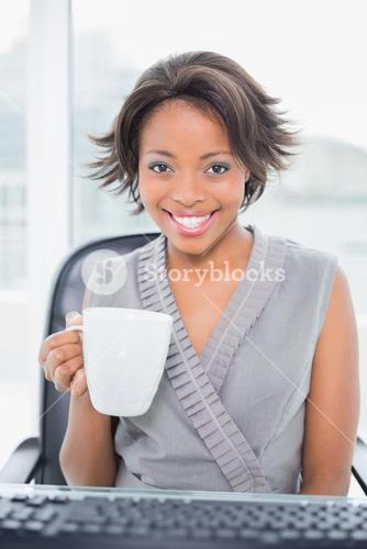 Smiling businesswoman holding cup of coffee and smiling at camera