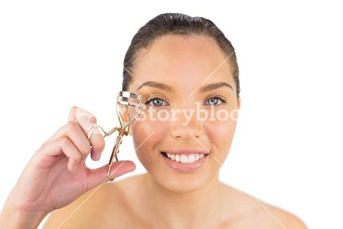 Smiling woman with eyelash curler