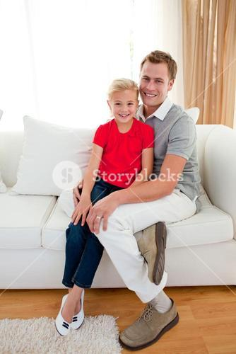 Blond little girl sitting on sofa with her father
