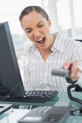 Angry businesswoman screaming while hanging up the telephone