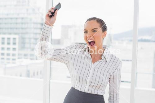 Offended businesswoman screaming and throwing her mobile phone