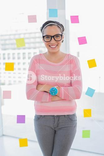 Happy woman with arms crossed in her creative office