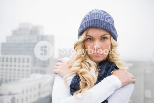 Shivering blonde in winter clothes posing outdoors