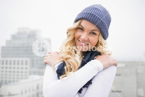 Smiling blonde in winter clothes posing outdoors