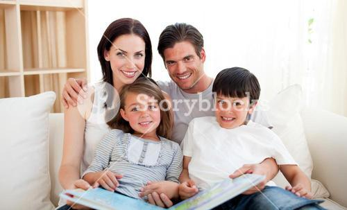 Family reading a book on the sofa