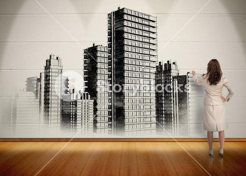 Businesswoman painting black and white city on wall