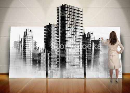 Businesswoman painting black and white city on screen