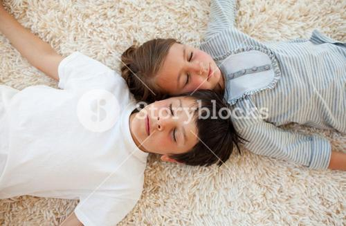 Siblings sleeping on the floor
