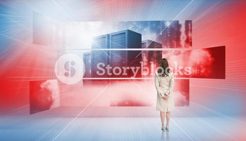 Rear view of businesswoman looking at screens showing server towers