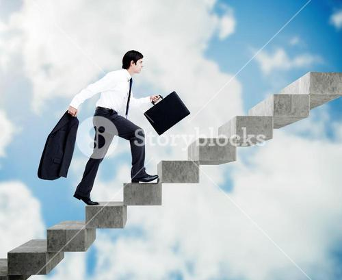 Young businessman climbing grey stairs