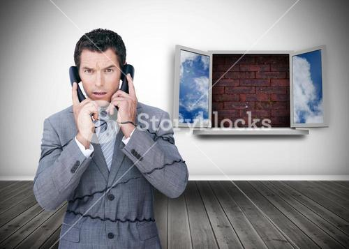 Frowning businessman wrapped in cables phoning