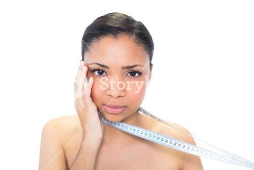 Worried young dark haired model holding measuring tape
