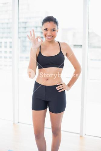 Happy dark haired model in sportswear making an okay gesture