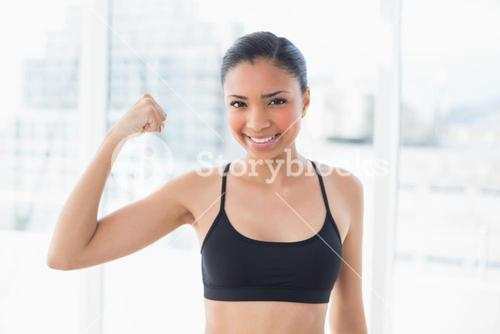 Happy dark haired model in sportswear contracting her muscles