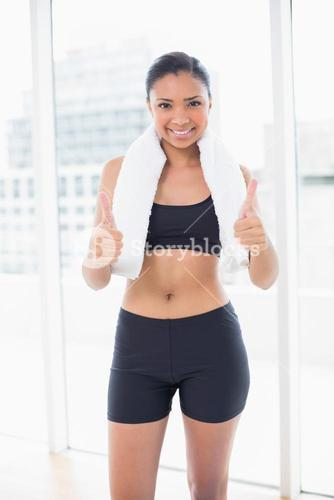 Confident dark haired model in sportswear giving thumbs up