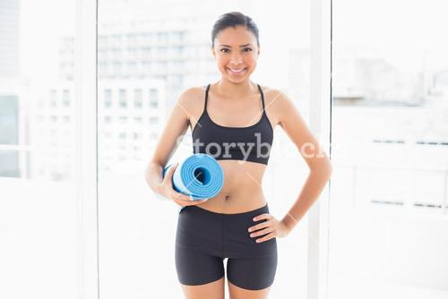 Smiling dark haired model in sportswear carrying a blue exercise mat
