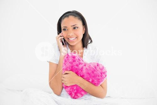 Pretty young dark haired model holding a pillow and making a phone call