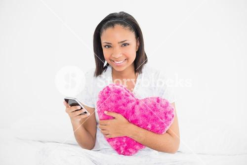 Delighted young dark haired model holding a pillow and a mobile phone