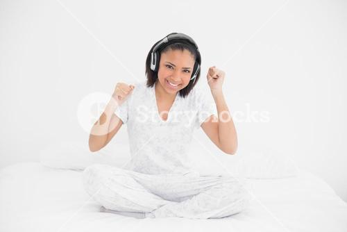 Dynamic young dark haired model listening to music with headphones