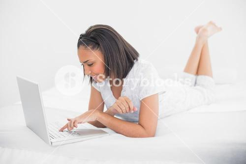 Content young dark haired model using a laptop