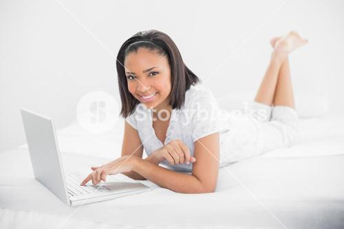 Pleased young dark haired model using a laptop
