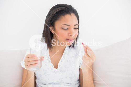 Unsmiling young dark haired model taking medication