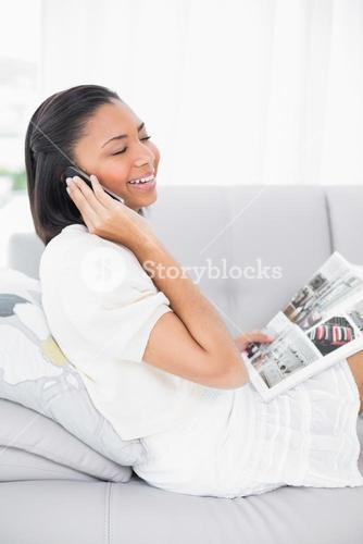 Delighted young dark haired woman in white clothes making a phone call