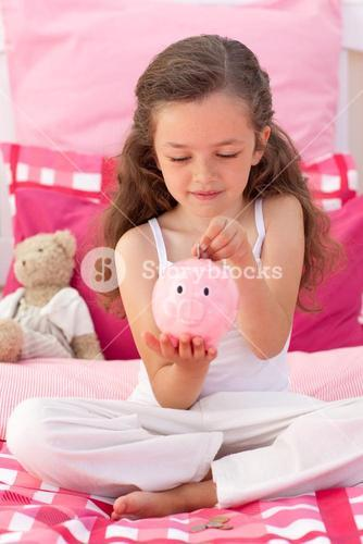 Smiling girl saving money in a piggybank