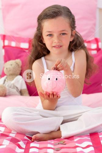 Little girl saving money in a piggybank