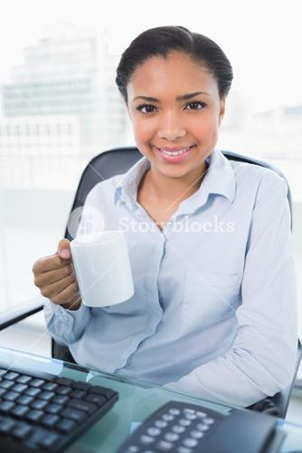 Content young dark haired businesswoman holding a mug of coffee