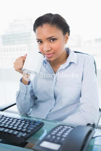 Pretty young dark haired businesswoman drinking a mug of coffee