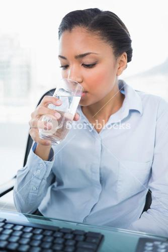 Calm young dark haired businesswoman drinking water