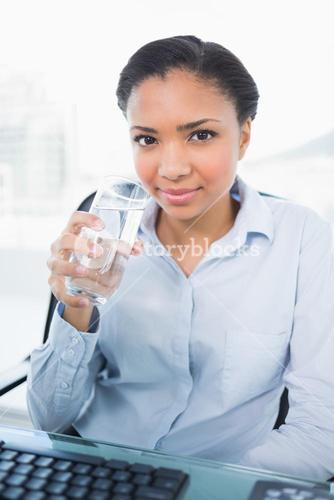 Smiling young dark haired businesswoman holding a glass of water