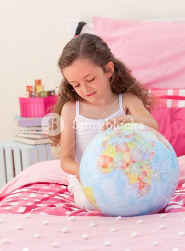 Little girl having fun with a terrestrial globe