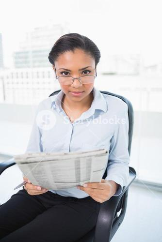 Lovely young dark haired businesswoman reading a newspaper