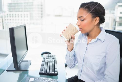 Relaxed young dark haired businesswoman drinking coffee