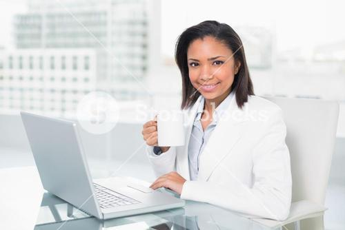 Cheerful young dark haired businesswoman using a laptop