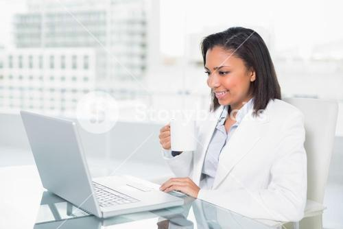 Pleased young dark haired businesswoman using a laptop