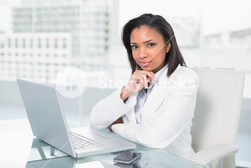 Attractive young dark haired businesswoman using a laptop