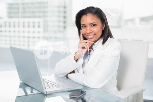 Dreamy young dark haired businesswoman using a laptop
