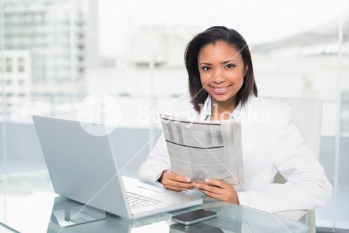 Cheerful young dark haired businesswoman holding a document