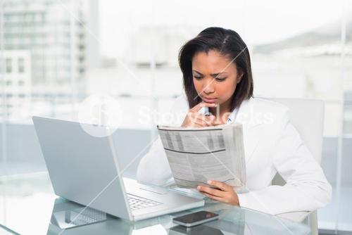 Concentrated young dark haired businesswoman reading a document