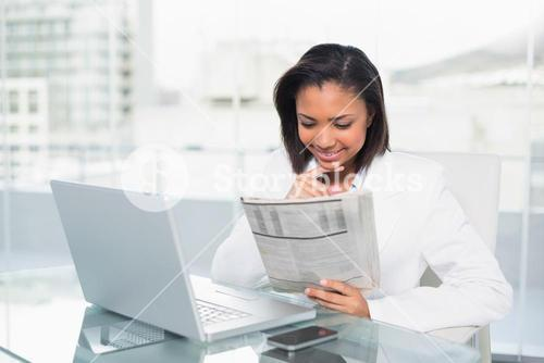 Amused young dark haired businesswoman reading a document